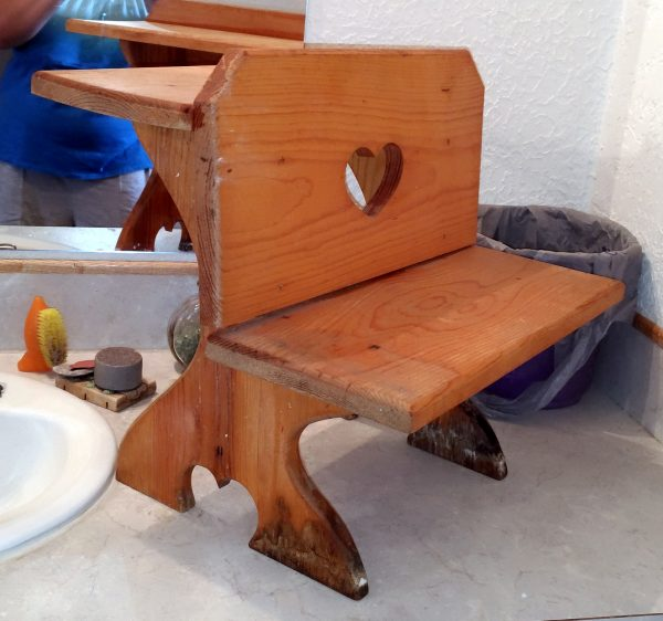 It's the kind of small stepstool that one's gransfather builds so that one can reach to wash one's hands when one is very small. There's a heart cut into the upright part.