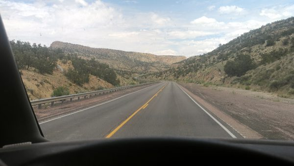 The road leads onward through scrubby hillsides under a blue sky studded with puffy white clouds. Photo taken from behind the wheel, which is just visible at the bottom of the shot.