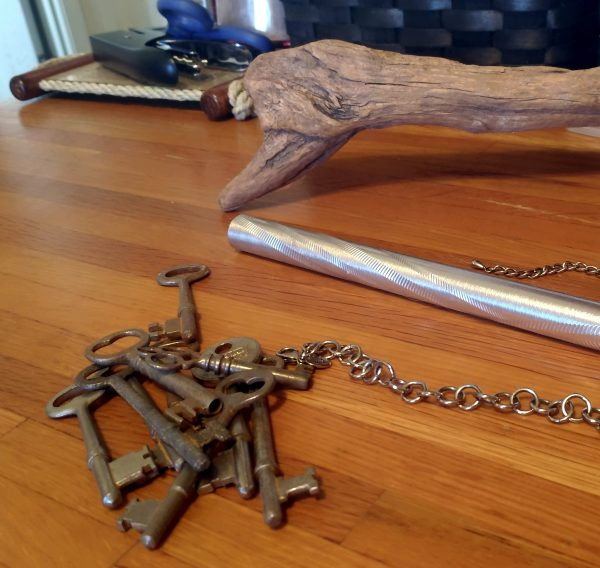 On a worktable, the stick, some keys, & a pretty silver tube chime from a windchime.