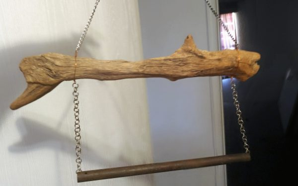 The duck stick is now hanging from a length of fine chain that's attached near each end; a different tube chime, this one not so pretty, hangs from the duck stick by two shorter lengths of chain.