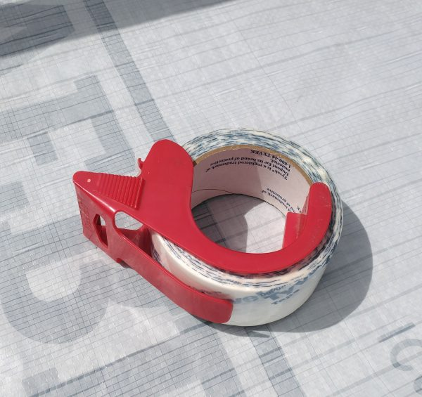 A layer of white plastic housewrap, with a small tape dispenser holding a roll of Tyvek brand tape.