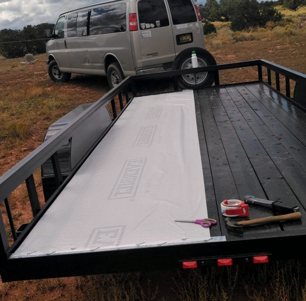 The trailer, with a length of housewrap laid all the way down the left side of the bed.