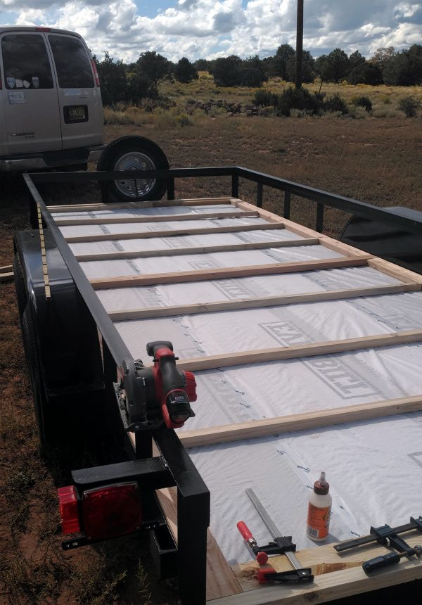 The trailer, seen from behind again, this time with a grid of 2x2 & 2x4 boards laid on top of the housewrap.