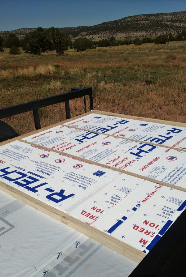 The trailer bed, with three of the floor sections fitted with foamboard insulation. Also in the background is desert scrub rising to low forested hills, the deep blue sky in the background.