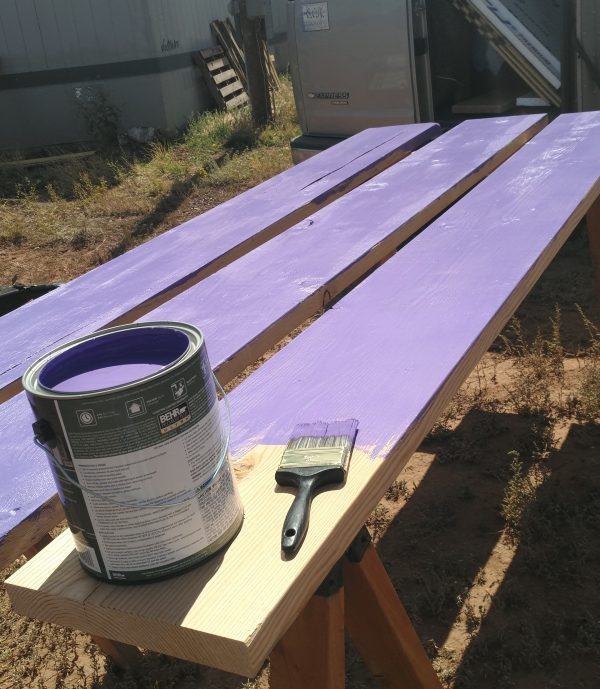 Three really wide boards sitting side by side on a pair of sawhorses. They've been painted purple except for the very end of one, which has a can of purple paint & a paintbrush sitting on it.