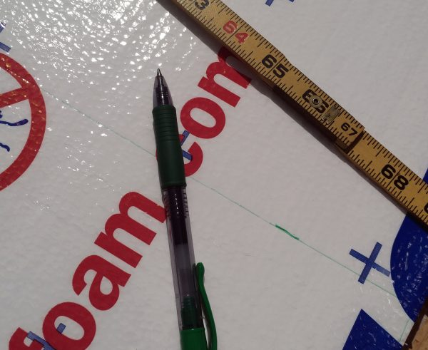 A green pen & ruler sitting on top of foamboard insulation.