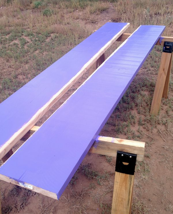 Two MORE 2x12 boards, laid across two sawhorses & painted purple on one side & most of the top. This makes sense, I swear.