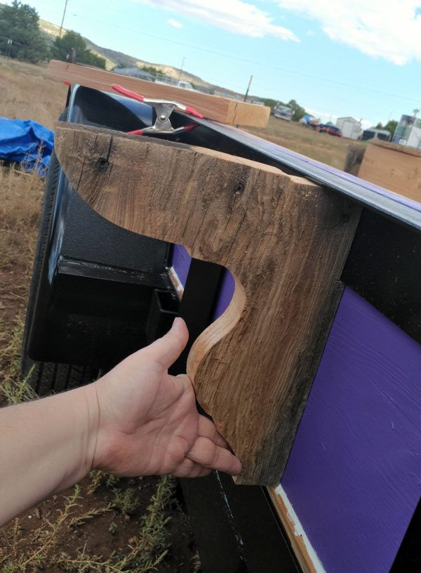 I'm holding the cut piece of wood up against the side of the trailer. It looks  cool there but the top edge of the brace is pretty not level.