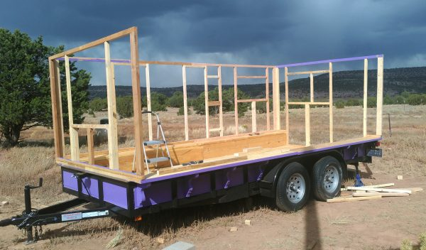 The tinker's wagon, seen from the side, with three of the walls framed out. The fourth, the one nearest, hasn't been done yet.