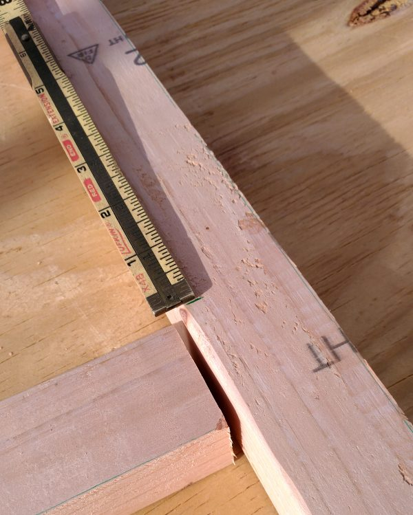 A closeup of two 2x2 boards butted together at right angles, with a ruler in place to mark the right spot.