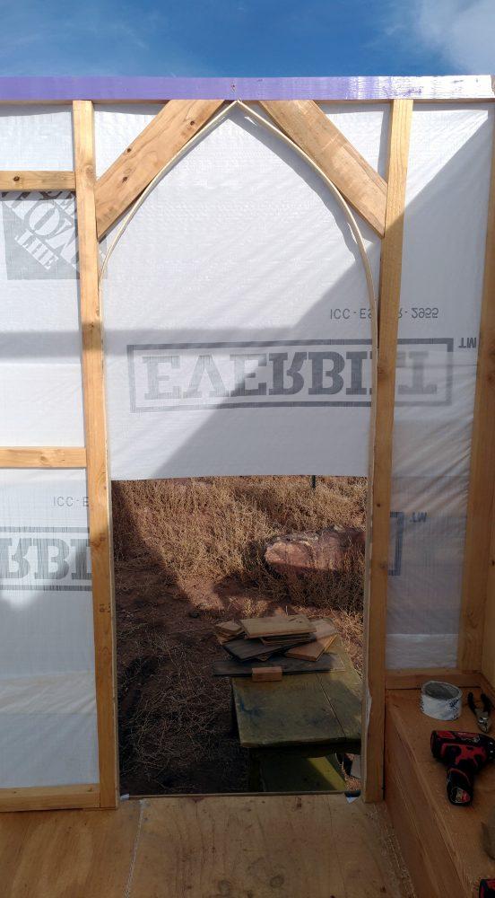 The front door frame, seen from inside. It's now arched at the top, & the bent plywood that makes the arch shape is braced by 2x4 boards set at a diagonal above it.