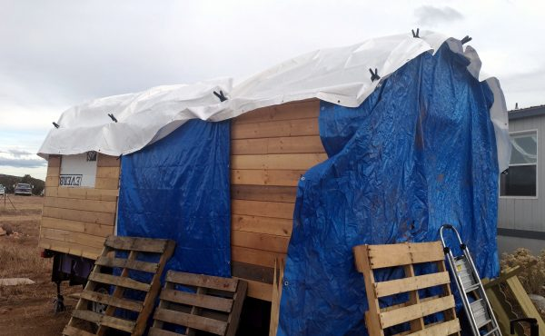The side of the wagon. You can still see some of the back, more of the roof is visible, & there's another blue tarp over the side door, with more pallets keeping it there.