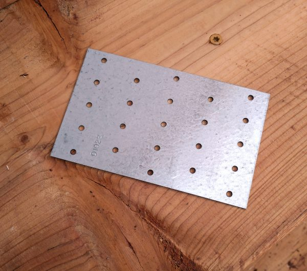 A flat, rectangular piece of metal, maybe four by six inches, with holes pierced in it for nails. Or screws.