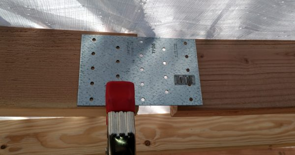 The metal piece is clamped in place along one end of a rafter, with half of it extending beyond the end & another rafter showing behind it.