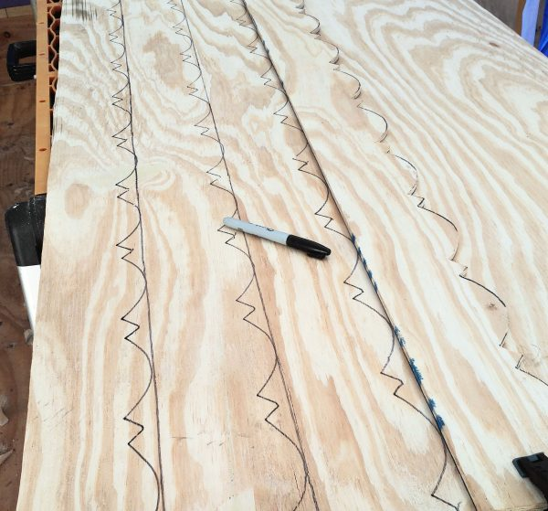 A sheet of plywood with outlines for fancy trim marked on them with sharpie. Also, there's a sharpie.