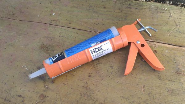 A tube of caulk in a Home Depot orange caulk dispenser.