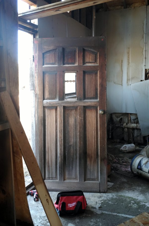 A beat-up but pretty fancy wooden door, inside a beat-up abandoned house.