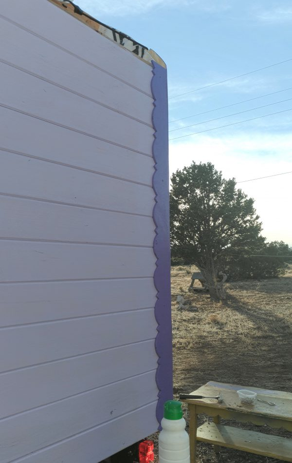 One of the front corners, seen from the side. The painted gingerbread trim runs vertically along the front corner.
