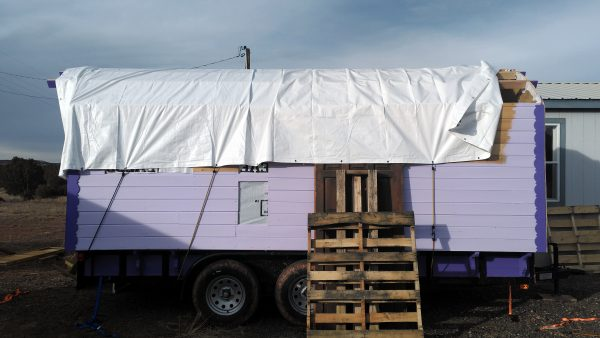 The right wall has been painted the same pale lavender to about halfway up, with the rest covered by the white tarp that also goes over the top of the wagon. An old wooden door covers the side doorway, & it's braced in place by two pallets.