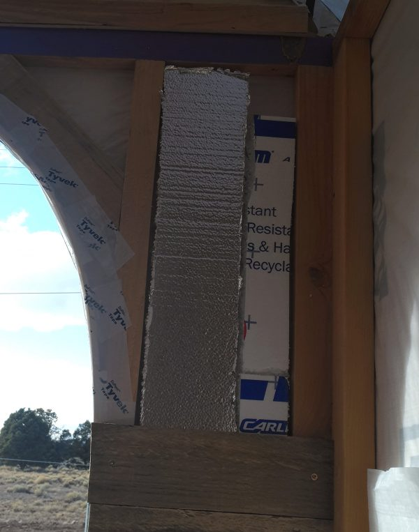 Further up the same wall. There are narrow pieces of styrofoam insulation tucked in between the 2x2 framing boards.
