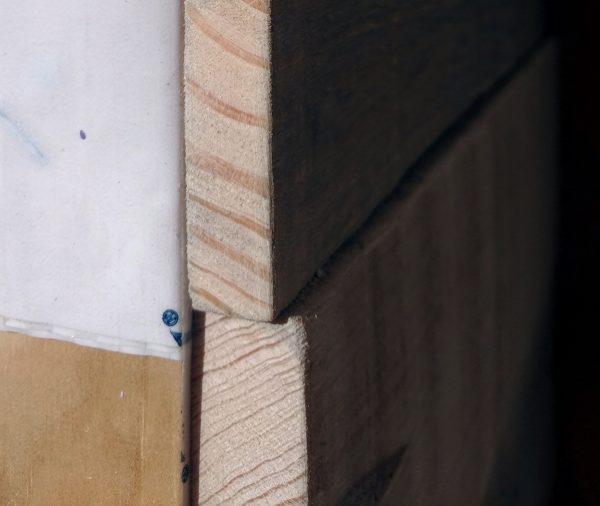 Two of the boards on the wall, seen from the edges. The bottom one is, indeed, thicker than the one just above it.