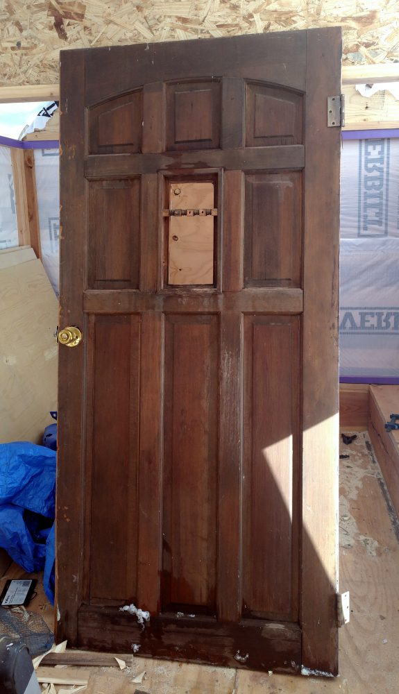 It's a really nice old door, the kind with the decorative inset panels. The middle panel is missing; I'm pretty sure there used to be glass there.