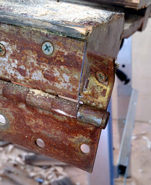 An old rusty metal door hinge, with a slot cut right the hell through the metal. Look, I was really excited the saw was working again, okay?