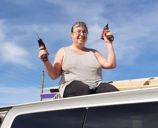 Me, a white person, kneeling on top of the van, as seen from below, I'm wielding a drill in each hand & have a probably terrifying grin on my face.