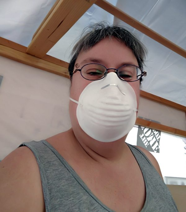 A selfie! Me, a white person with brown bangs, wearing a grey tank top & a cheapass white face mask that covers my nose & mouth. I look THRILLED.