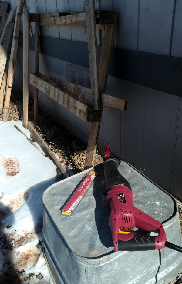 A reciprocating saw sits on an overturned metal tub; behind that, a partly disassembled pallet leans against the house wall.