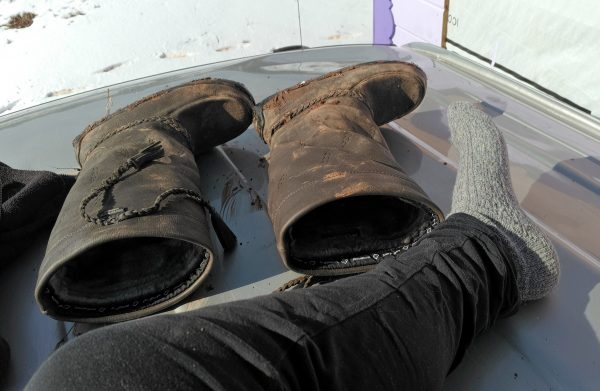 A really great pair of Manitobah Mukluks boots lay on the roof of the van. In front of them is my leg. I'm wearing black leggings & a grey wool sock. Well, two, but only one is in the picture.