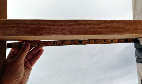My hand, holding a folding ruler along a 2x4, with the sky in the background.