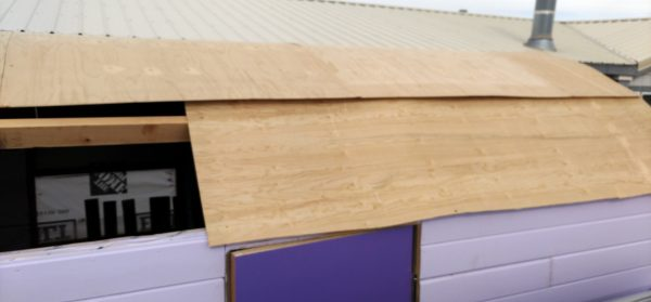 A view of the back half of the tinker's wagon's roof, from the side. Nearly all of it is covered in plywood now, but there's a gap to the left side, at the base of the roof.