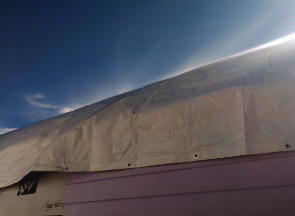 The side of the tinker's wagon. Yep, there's a tarp bungeed over it.