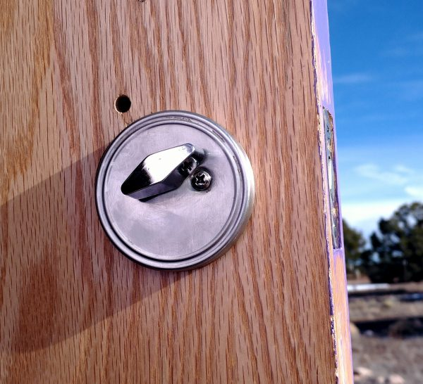 It's the latch side of a silver-coloured deadbolt, & it's neatly fastened to the door.