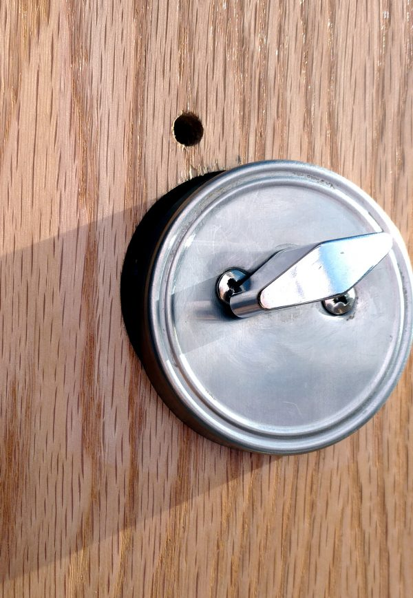 Seen at a different angle & closer up, it becomes speedily clear that the deadbolt is off-center in the hole it's supposed to go through, leaving a crescent-shaped gap on one side. Oops?