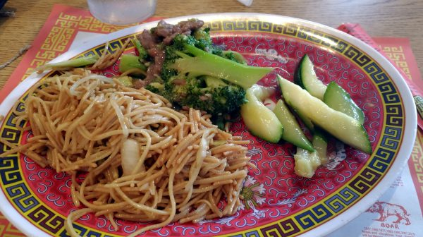 An oval plate holds a pile of noodles, broccoli, & zucchini.