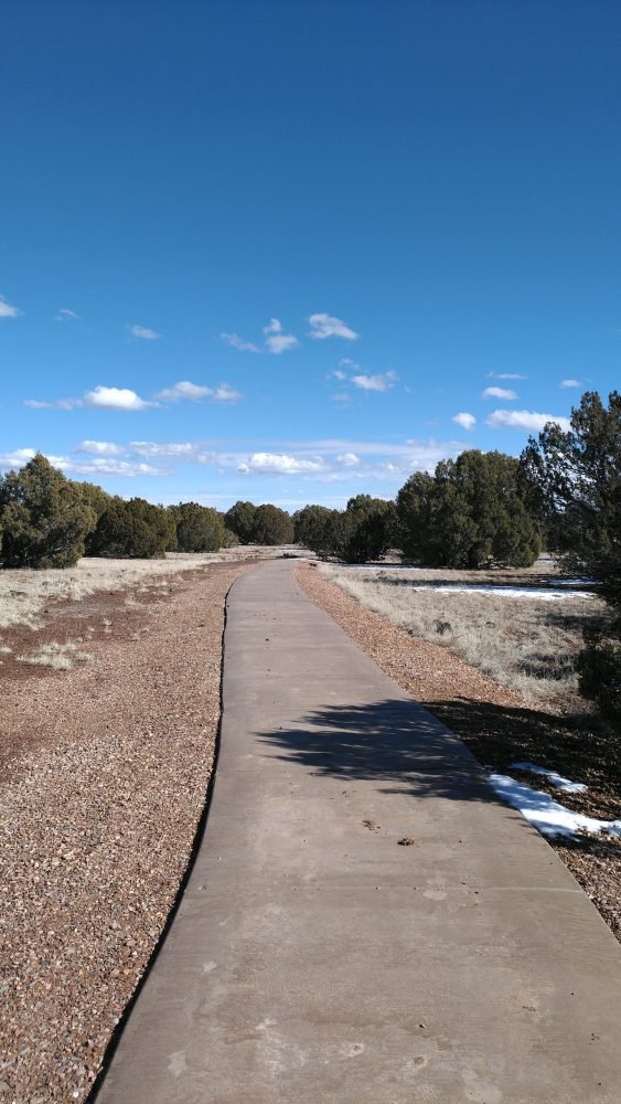 A concrete path leads in a gentle curve through low desert brush dotted with evergreens, below a blue sky.