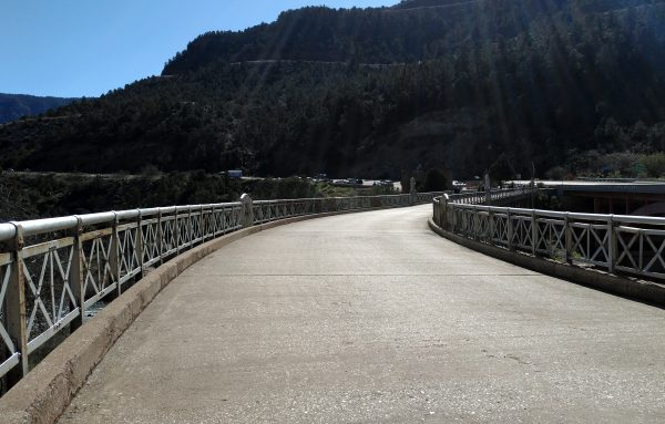 The photo is taken from on the old bridge, which curves attractively off to the right. The pavement is pale & a bit pebbly; beyond the bridge rises a forested hill.