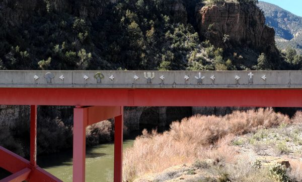 The new bridge, seen from the side. The supporting arches holding up the roadbed are painted red; the railing is concrete, but it has shapes cut into it -- arrowheads & stylized saguaros.