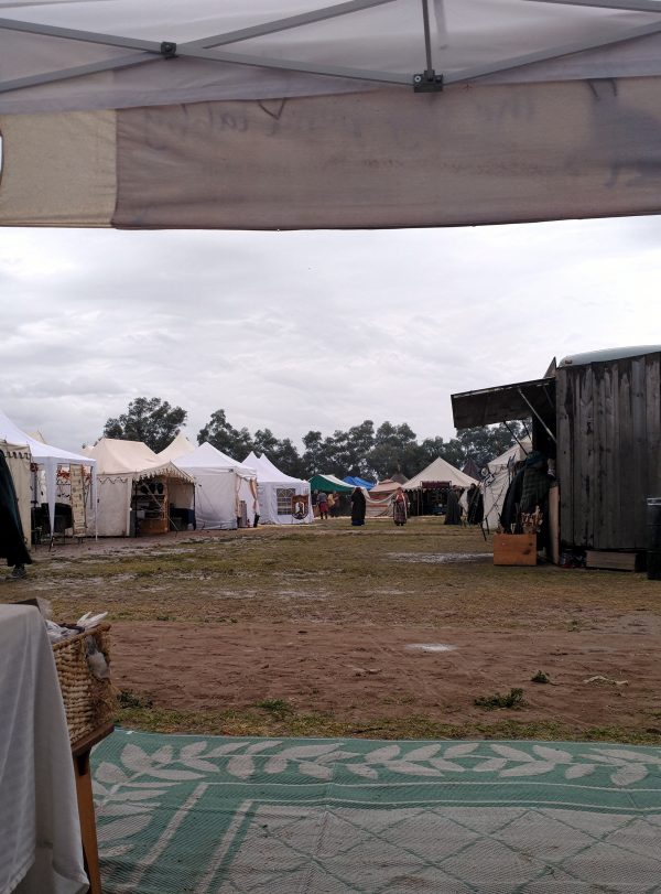 The view out the front of the booth. To the right is another trailer booth, this one with weathered wooden walls. A row of canvas tents line the left side of the road. The sky is grey & there are a few small puddles on the ground.