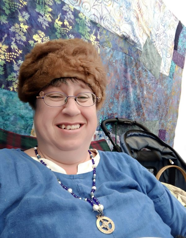 Me, out of bed this time. I'm sitting in the booth, up against the quilt decorating the back wall. I'm wearing a blue dress & a nice warm fuzzy hat.wearing a blue dress
