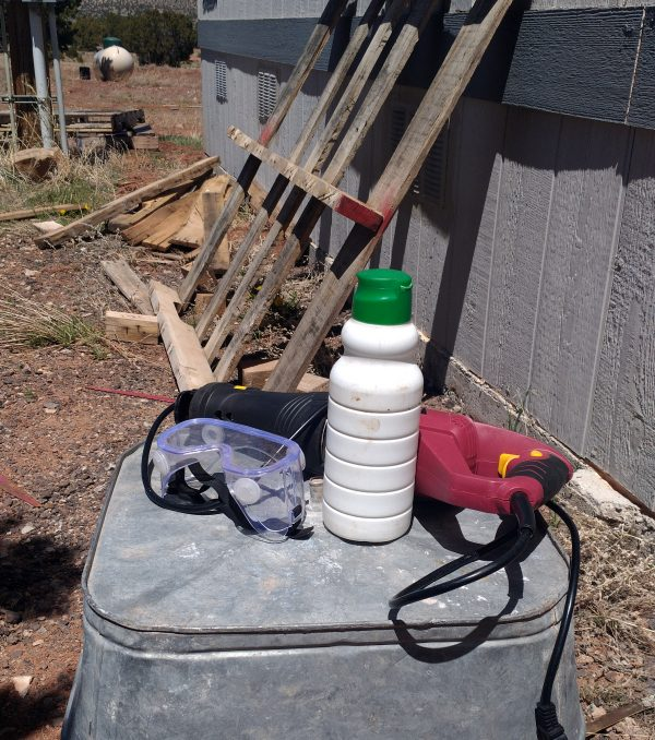 The sawzall in question is sitting on an overturned washtub, along with a bottle of water & a pair of safety goggles. I forgot to actually use the goggles, mind you. In the background a partially-disassembled pallet leans against a wall.