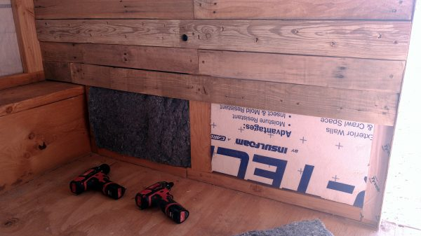 The wall is covered in boards except for the bottom foot or so. Some white styrofoam insulation is visible below that, & also some vaguely jeans-coloured denim insulation.