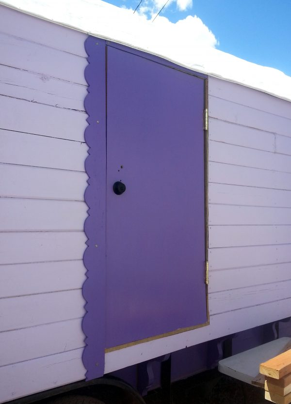 Tyrava's side door. It's painted a dark purple, & has matching dark purple trim down the left side. Also, the bottom is about a foot anna half off the ground.
