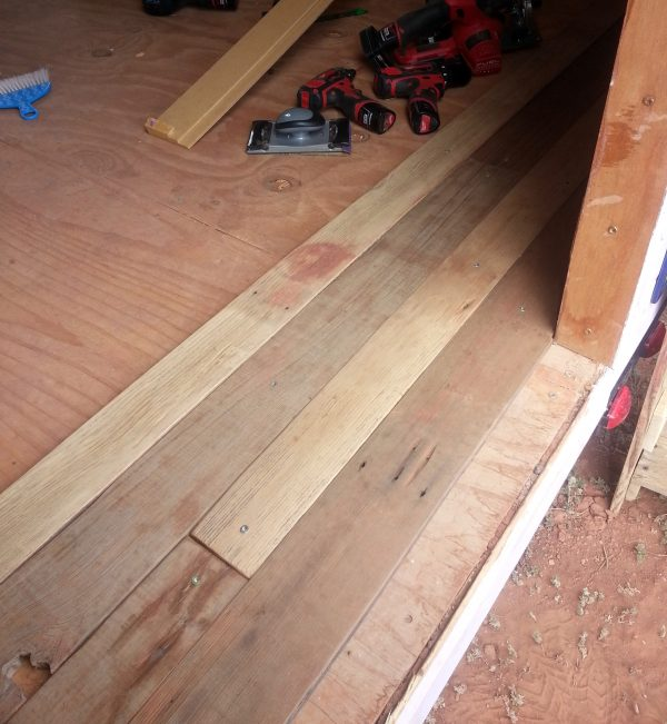 Four rows of boards have been fastened to the floor inside Tyrava's front door, each stretching across the width of the floor. They're different widths & different shades of brown.