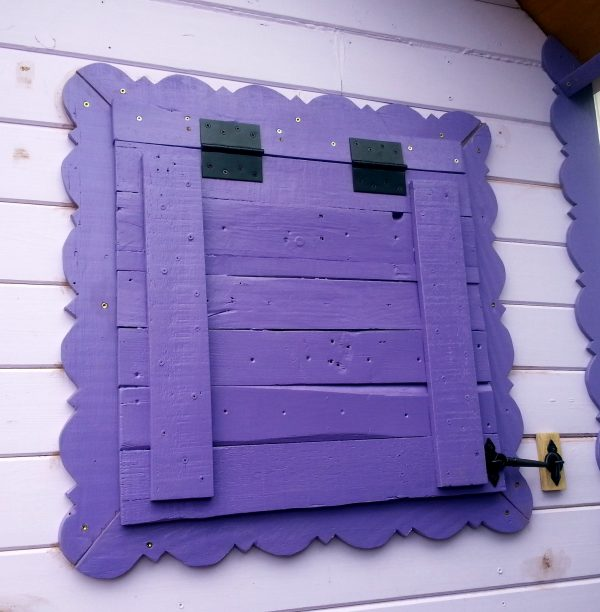The latch is fastened to the lower right corner of the shutter. It matches the hinges, & looks pretty good.