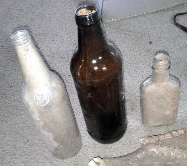 Three glass bottles. The lefthand one is clear & about the size of a wine bottle; the center one is brown, the same shape as the first but larger around; the shirt is maybe half the height, clear, & flattened like a flask.
