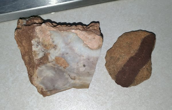One rock is smooth & white, with patches of rougher pinky-tan. The other is rough, mostly pale orange, with a brown stripe running along it.