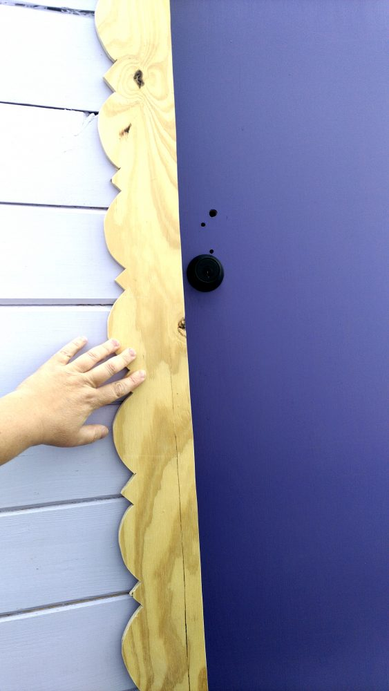 The trim piece, being held up along the edge of a deep purple door.